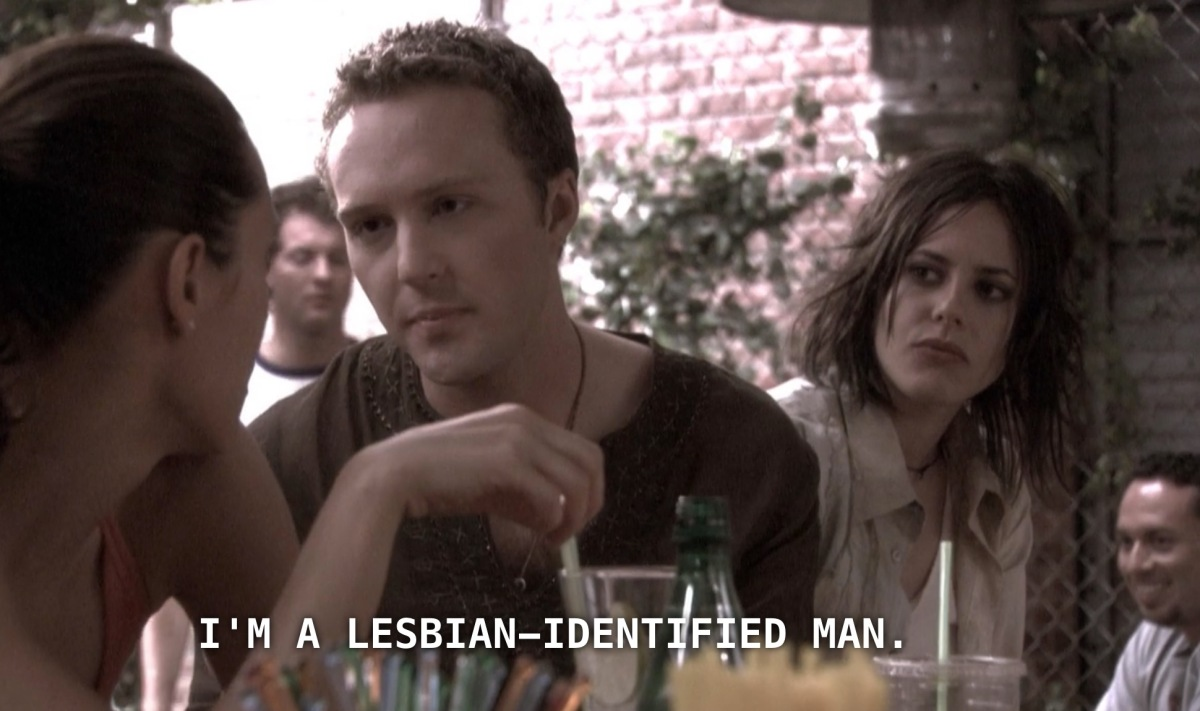 "Lisa stares earnestly at Dana, with Shane looking on skeptically in the background. Lisa, who is wearing a brown thermal knit tee and has short brown hair, says to Dana, ""I'm a lesbian-identified man."""