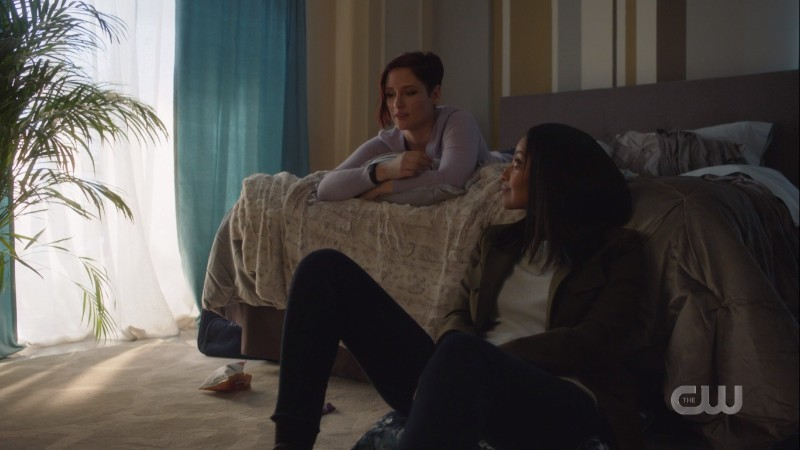 Alex is on the bed and Kelly is sitting in front of it