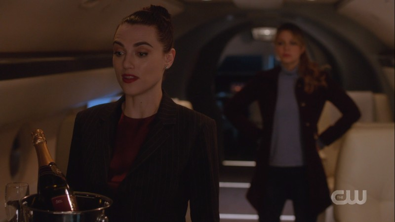 Lena talks while Kara has her glasses off and is in supergirl stance behind her