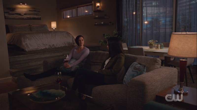 Alex and Kelly are on Alex's couch with red wine