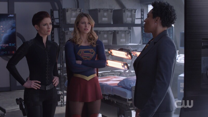 Alex stands with her hands on her hips, Supergirl with her arms crossed