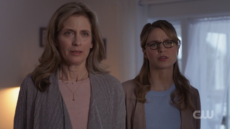 Red Daughter dressed as Kara looks mad, standing behind Eliza