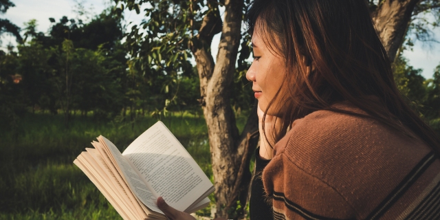 A femme person reading a paper book outside.
