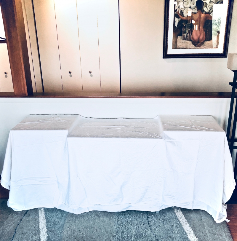 A living room table covered in a plain white tablecloth.