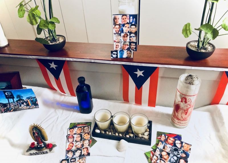 A home photograph of an altar built in a living room with a collection of white table cloth, candles, and Puerto Rican flags.
