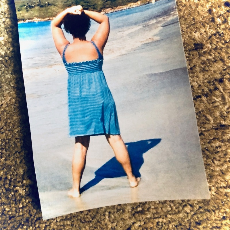 A photograph placed against a textured background of the author in a blue sundress in Puerto Rico