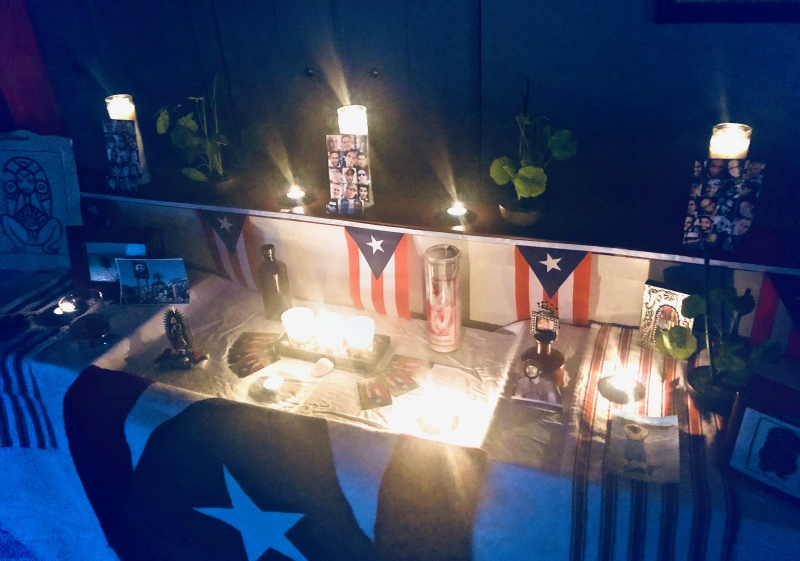 A home photograph of an altar built in a living room with a collection of white table cloth, candles, and Puerto Rican flags. The photograph is in the dark with candles lit.