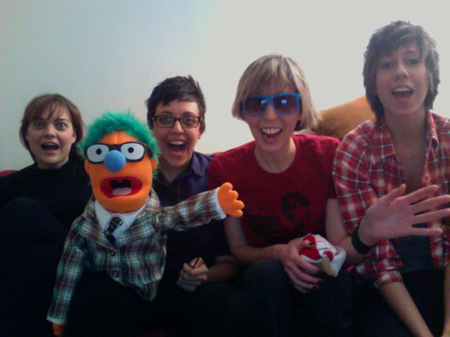 A throwback picture of the early days of Autostraddle. Robin Roemer (wearing a black turtle neck and brown hair with bangs), Carly Usdin (wearing a blue button-up, short brown hair, and glasses), Riese Bernard (wearing a red t-shirt, blue sunglasses, and a blonde gay haircut), and Alex Vega (wearing a red plaid shirt and a brown very gay haircut) sit on a couch, all with their mouths excitedly agape. Carly is holding a bright orange puppet guy with glasses, teal hair, and a blue nose.