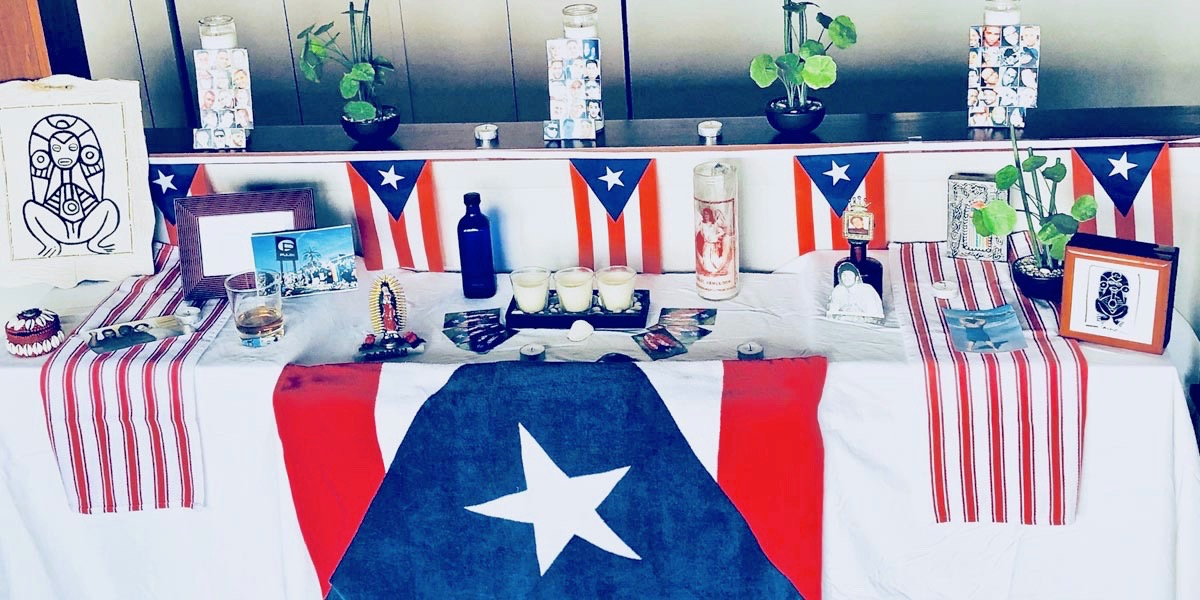 Honoring the Pulse Nightclub shooting on its anniversary: A home photograph of an altar built in a living room with a collection of white table cloth, candles, and Puerto Rican flags.