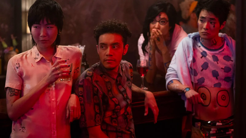 Image: four hipsters at a bar at night