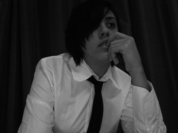 A picture of your host, Carly Usdin, from 2007. They are wearing a white button-up shirt and a skinny black tie. They have an extremely gay asymmetrical haircut and have one finger demurely in their mouth as they stare off into the distance.