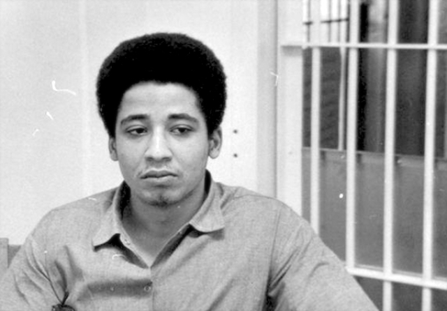 A photo of George Jackson, founder of Black August, incarcerated inside his prison cell.