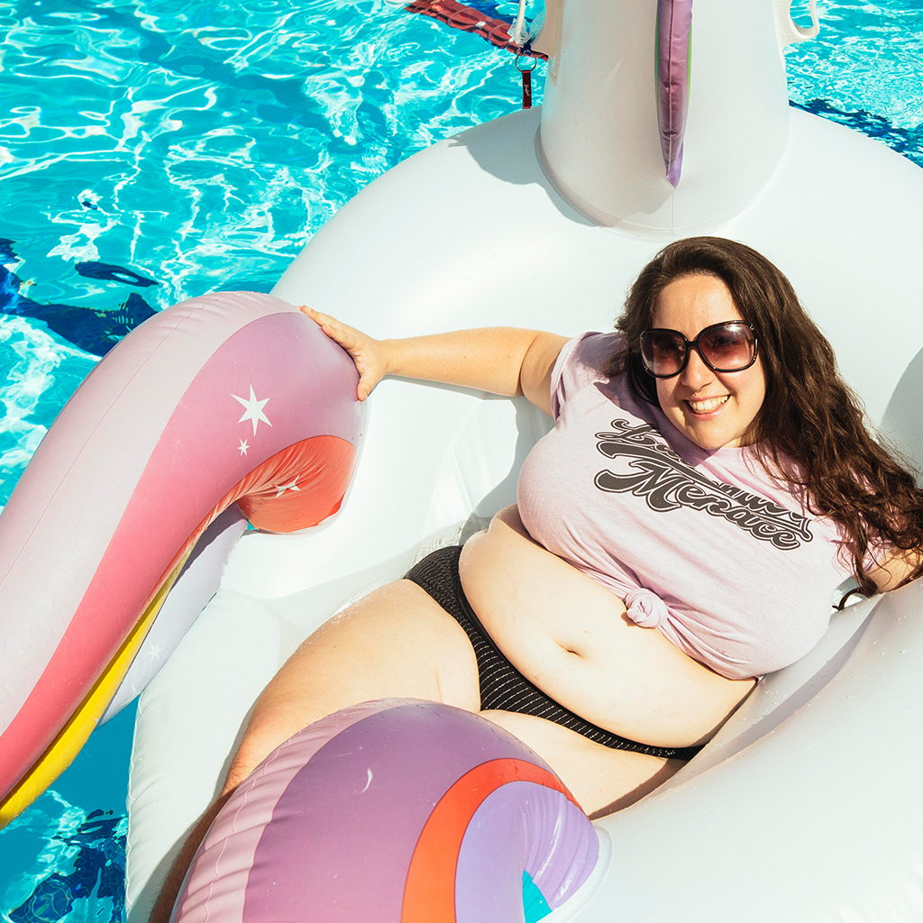 Vanessa laying on a unicorn float in a pool wearing our Lavender Menace Tee