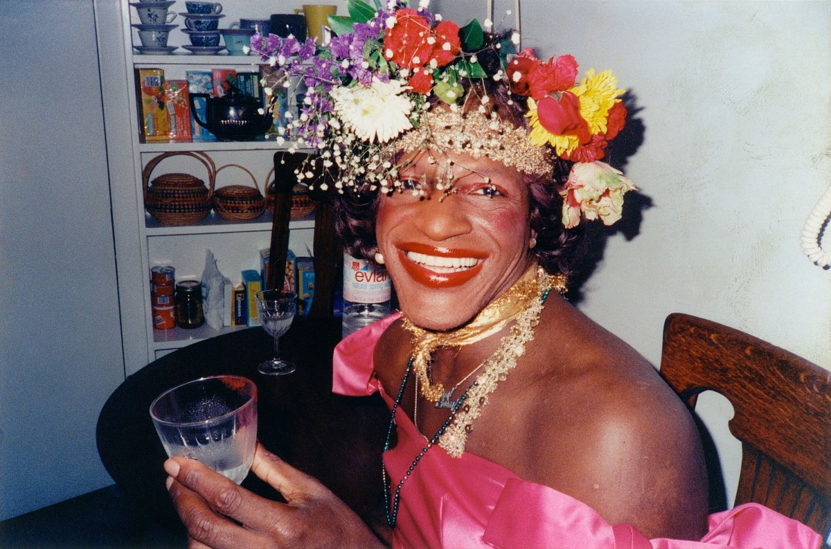 A glamour photo of Marsha P. Johnson in her famous flower crown and a pink dress.