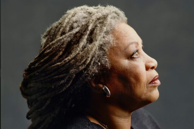 An iconic and famous portrait of Toni Morrison, looking off camera, with her grey dreadlocks pulled into a low bun just past her shoulders.