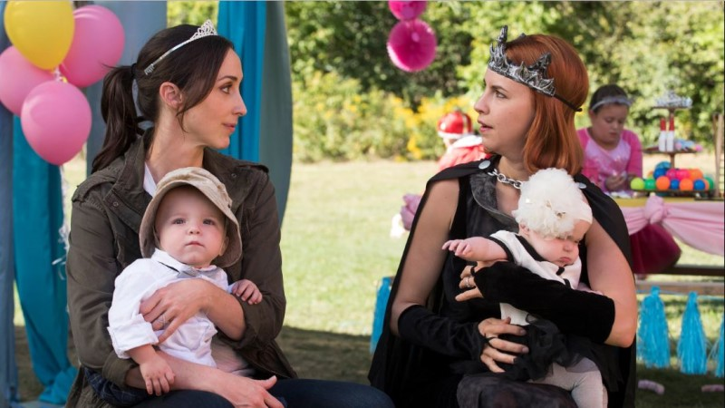 Anne and Kate at a child's birthday party having a serious conversation wearing silly crowns