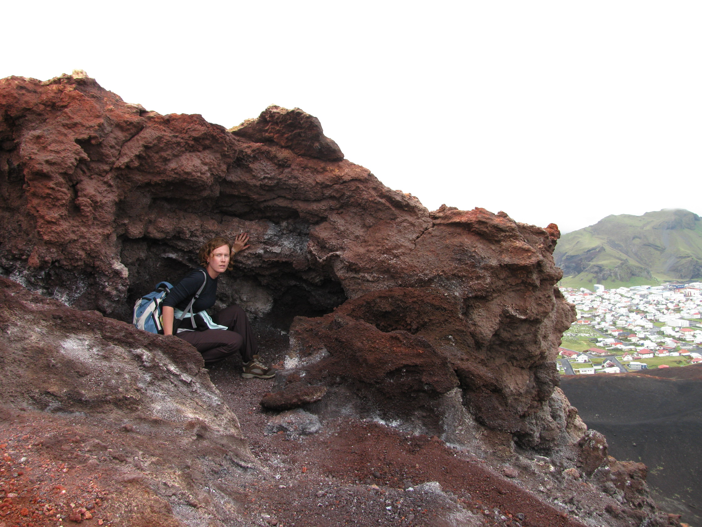 The author is crouching inside a small recess in a large jagged red rock at the top of Eldfell, with her hand extended to touch the side. There is a glimpse of the town and another mountain in the distant background.