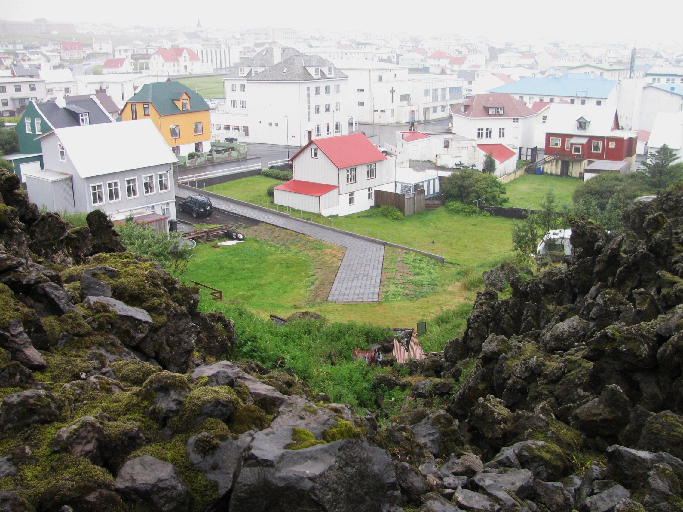 View over Heimaey town showing several white and multicoloured buildings in fog, and a dead-end street ending at a ridge of jagged boulders covered in grass and moss.