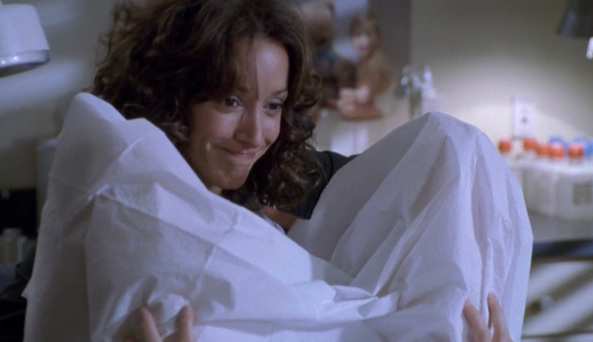 Bette about to go down on Tina who is draped in a hospital gown