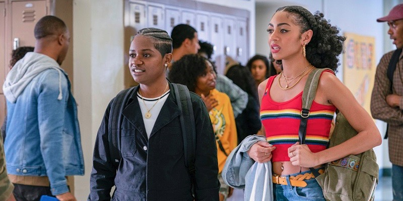 image: coop, a Black masculine-of-center lesbian with her hair in braids is wearing a hoodie and a backpack in a school hallway. Next to her is a taller girl with her hair in a ponytail and a striped tank top. there are students and lockers in the hallway.