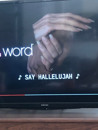 "A photo of a freeze frame of The L Work on a flat screen TV sitting on a brown wooden table. It is paused to show a series of hands (with fingernails that are far too long) intertwined. The subtitles show that a song is playing with the lyrics ""Say hallelujah."""