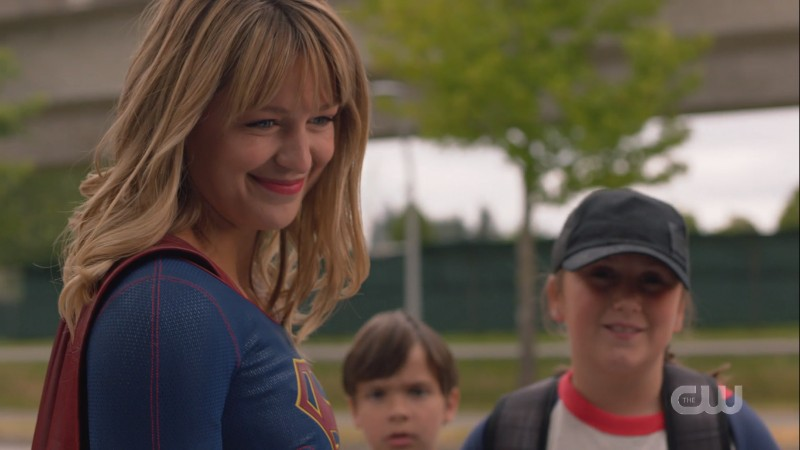 Supergirl smiles at the children she saved