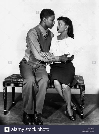 A black-and-white photo, featuring a Black man (wearing trousers, a button-up and tie, and a vest) locking arms with a Black woman (wearing a black skirt and white top) as they sit on a bench and stare into each others' eyes. This is a stock photo that appeared in the background of this episode of The L Word.