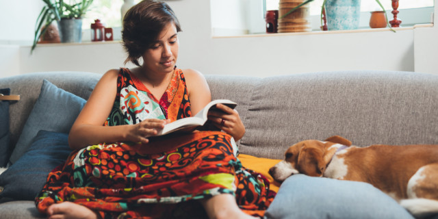 A person reading on a couch in a dress with a dog asleep next to them