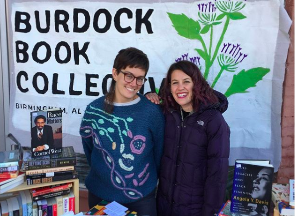 Two people stand in front of a sign reading Burdock Book Collective, smiling at the camera
