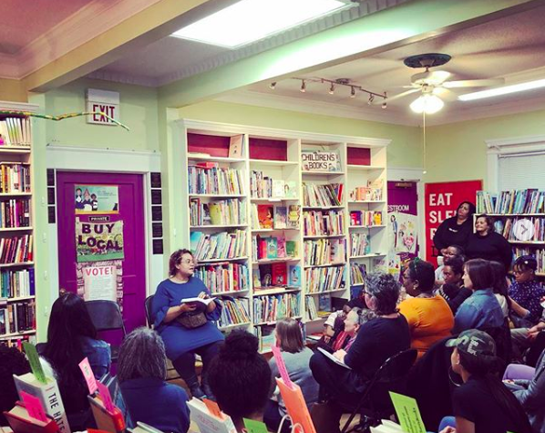 A seated person reads from a book to an assembled gathering of listeners, with bookshelves and a sign that reads BUY LOCAL on the walls behind her