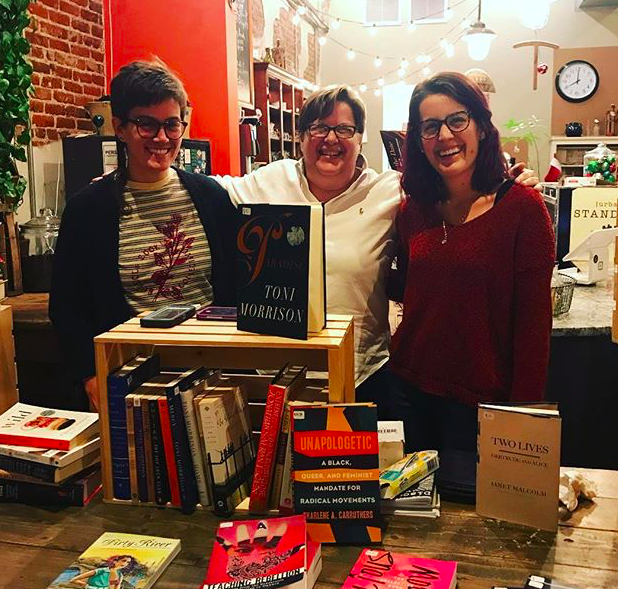 Three people stand behind a display table of books; the person in the center has her arms around the respective shoulders of the two people on either side of her, smiling