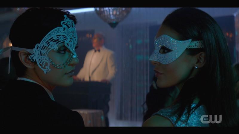 Bess and Lisbeth exchange glances in masquerade masks
