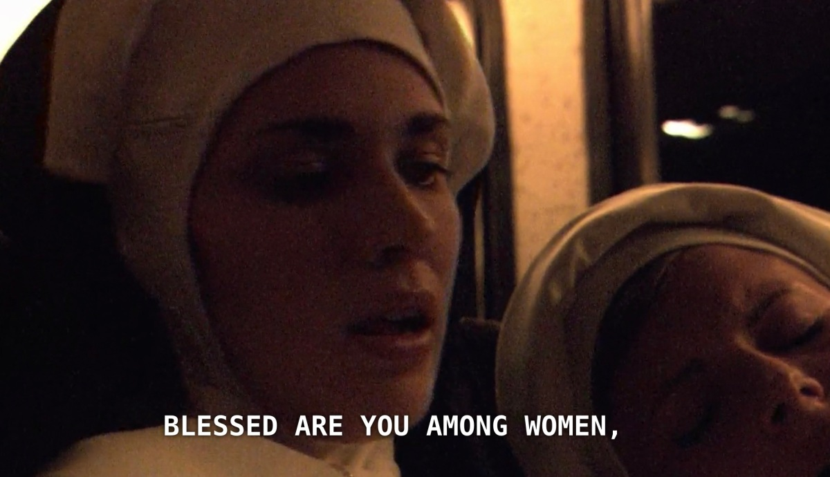 "A nun riding on a charter bus, wearing nun attire and her mouth slightly open, saying ""blessed are you among women."" Another nun sits asleep next to her."
