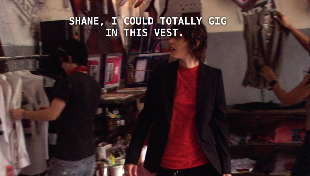 "Shane stands in the skate shop, wearing a red t-shirt underneath a black blazer. Carmen is standing behind her. Carmen found a vest and says to Shane, ""I could totally gig in this vest."""