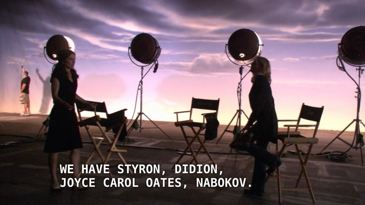 "Helena and Tina stand in a big film studio with directors chairs and spotlights shining on a backdrop of clouds. Helena is detailing the success of her publishing company, saying that ""We have Styron, Didion, Joyce Carol Oates, Nabokov."""
