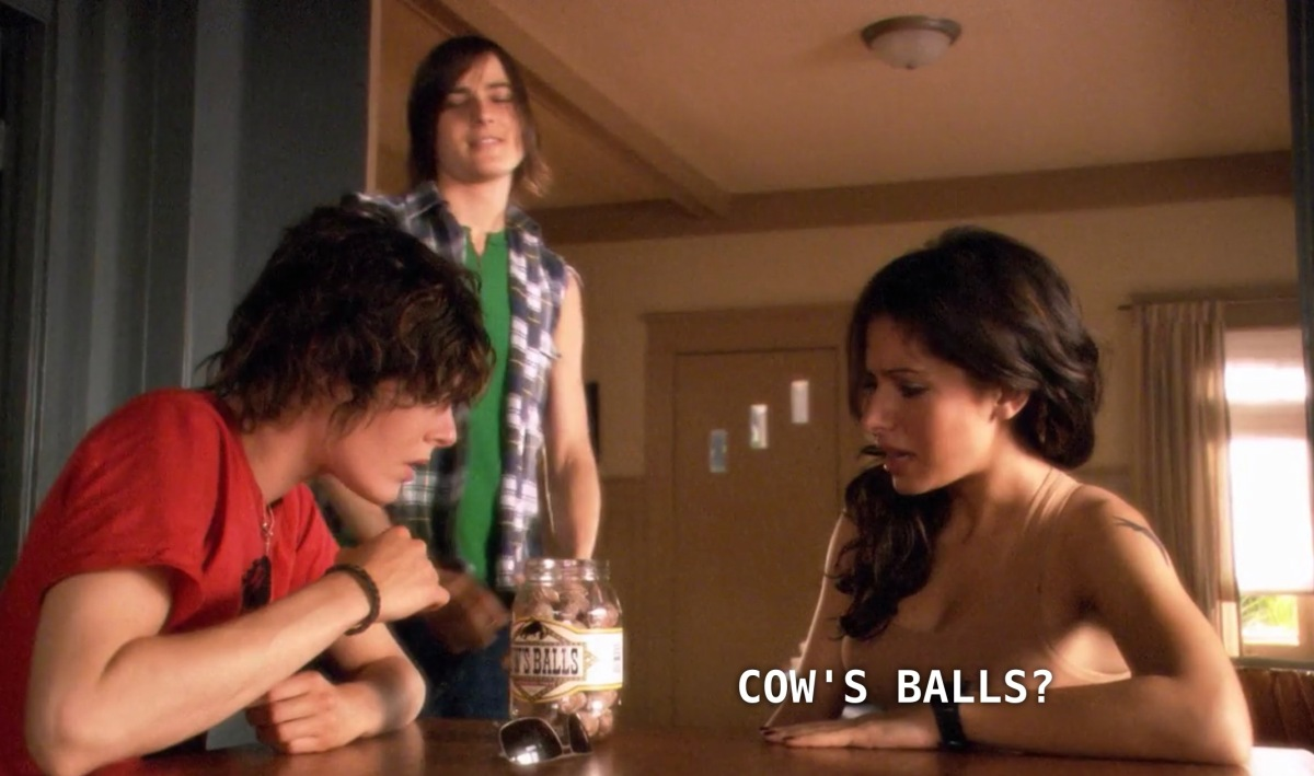 "Shane and Carmen sit at the kitchen table inside Shane's house. Max stands next to them. Max has just given Shane and Carmen a present, a jar that is labeled ""Cow's Balls"". Max takes a ball out of the jar and pops it into his mouth, as Carmen asks skeptically, ""Cow's Balls?"""