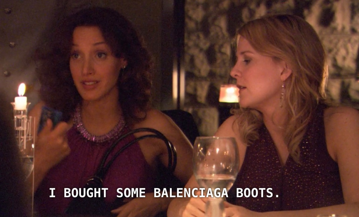 "Bette (wearing a purple cocktail dress) sits to the left of Tina (also wearing a purple cocktail dress, but darker than Bette's). Bette says, ""I bought some Balenciaga boots"""