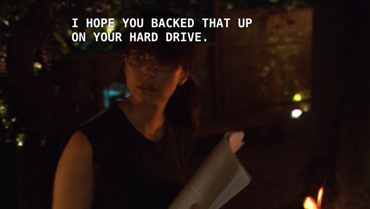 """Jenny, wearing a black tank top and glasses with her hair in a ponytail, sits outside holding her manuscript as she adds page after page to a burning fire. Off screen, Max says, """"I hope you backed that up on your hard drive."""""""