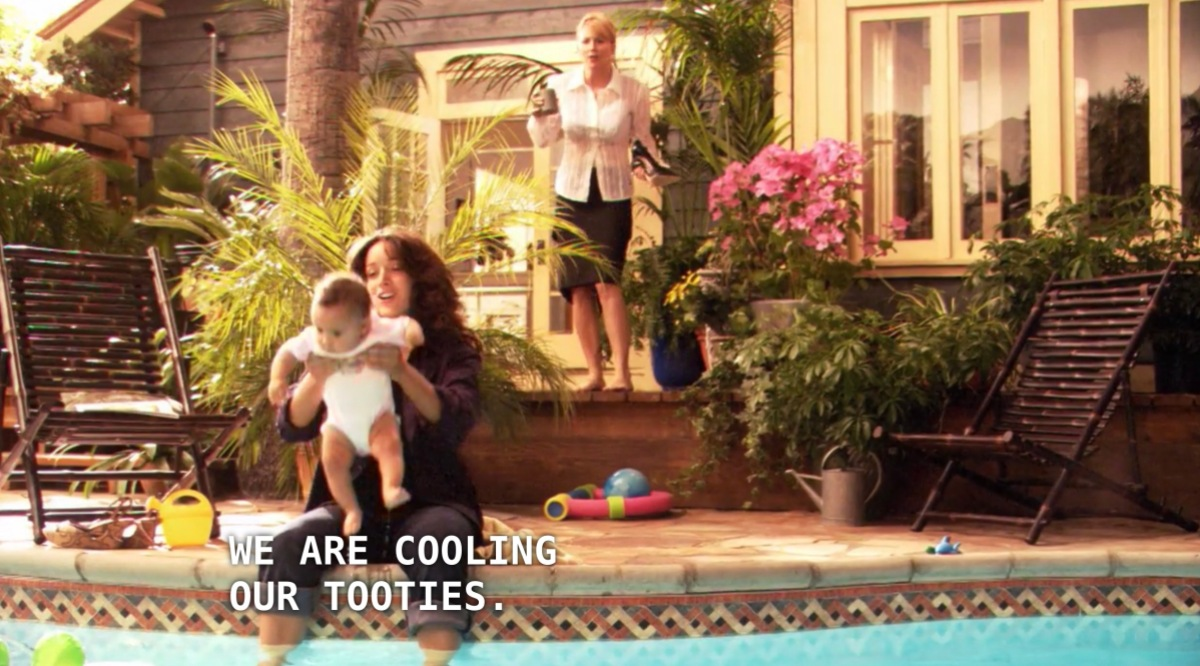 """Bette is holding Angie while she sits with her feet dangling over the edge into her backyard pool. Tina stands behind her, wearing a black skirt and white button-up. Bette says to Tina, """"we are cooling our tooties."""""""