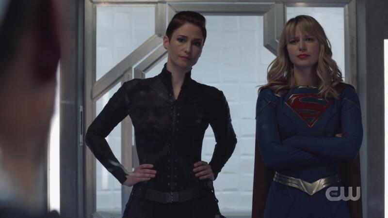Alex and Kara look sternly upon their prisoner