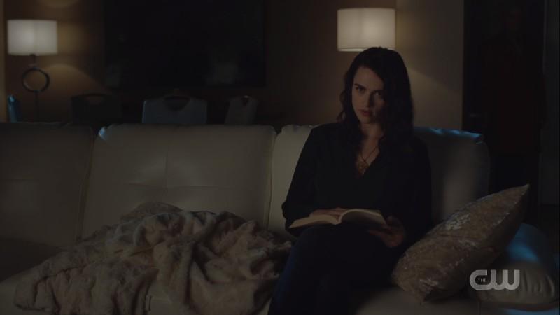 Lena sits reading in the dark