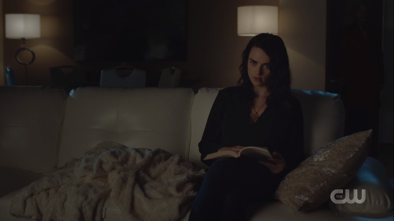 Lena sits reading in the dark