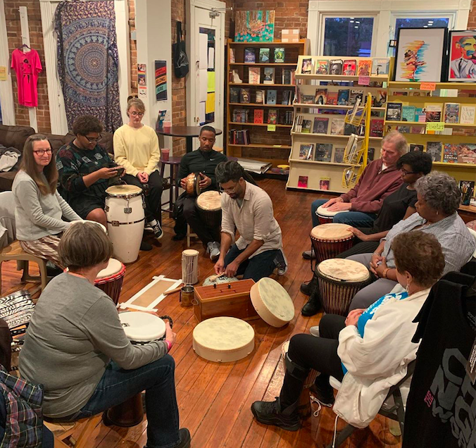 A group of a dozen or so people sit in a circle with drums before them, a row of bookshelves behind them