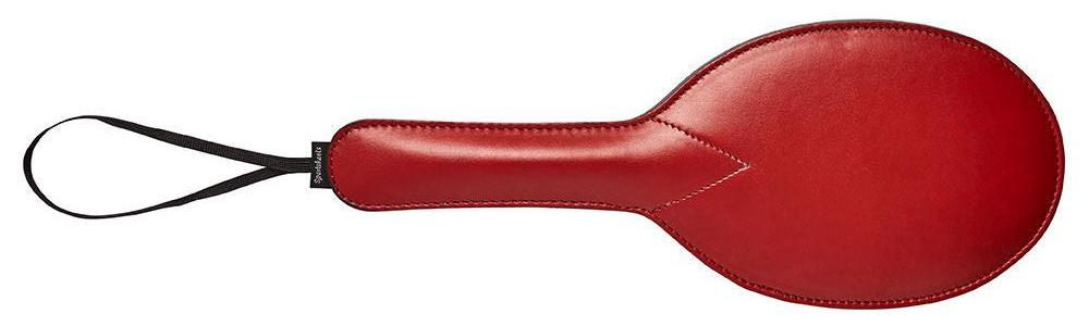 an oval red leather paddle with a loop for hanging
