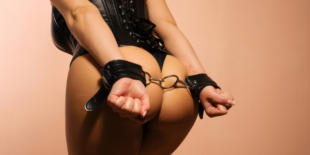 a femme in a corset and handcuffs. photo is mostly of the model's butt with hands cuffed over it.