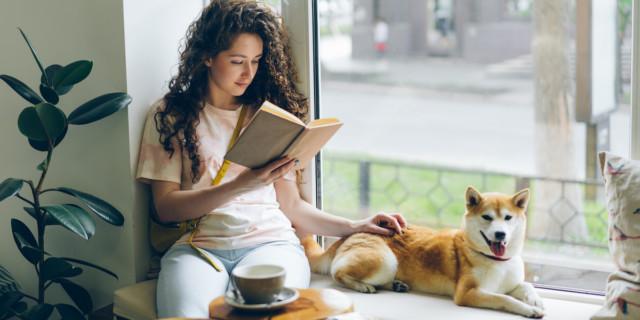 A woman with long curly hair reading in a window, with a tea cup in a saucer and a mid-sized shorthaired dog