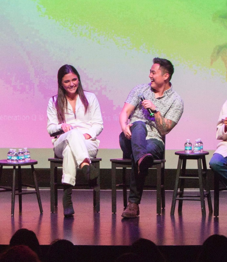 Arienne Mandi and Leo Sheng sit next to each other on stage. They are both laughing.