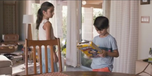 Eli reads the back of a cereal box while his sister Olive walks by.