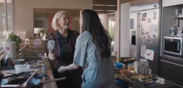 Alice holds a spatula in the kitchen with her girlfriend Nat