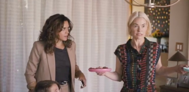 Nat's ex-girlfriend Gigi looks at Alice, who is shrugging while holding a pink plate